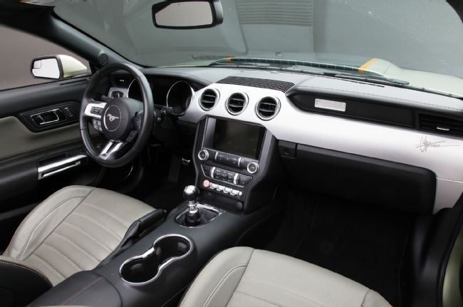 L'intérieur dispose de sièges en cuir vert et « charbon de bois » personnalisés avec des surpiqures orange.
